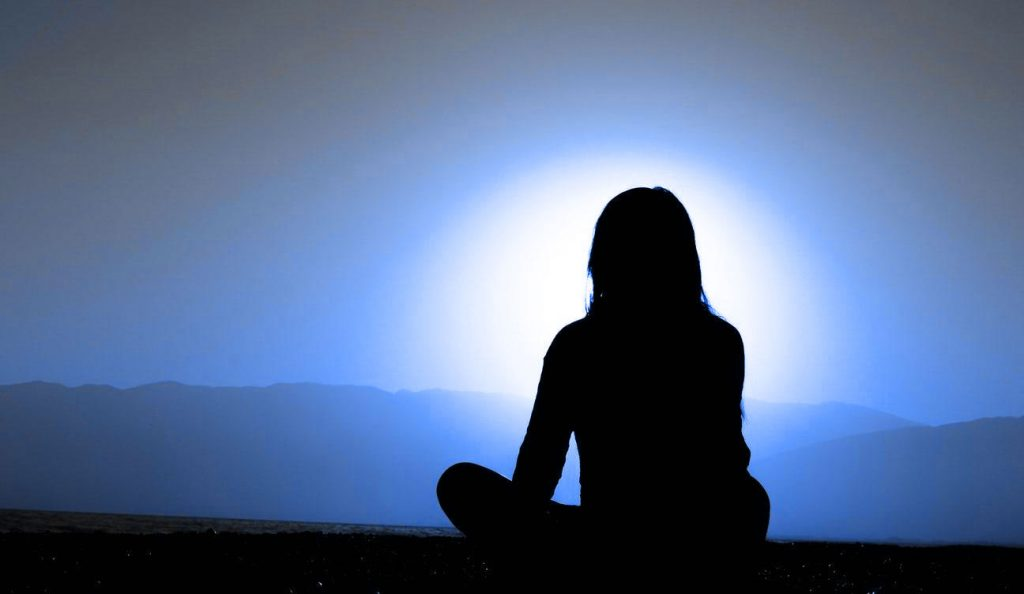 Woman seated cross-legged in meditation against a blue tinged mountainscape