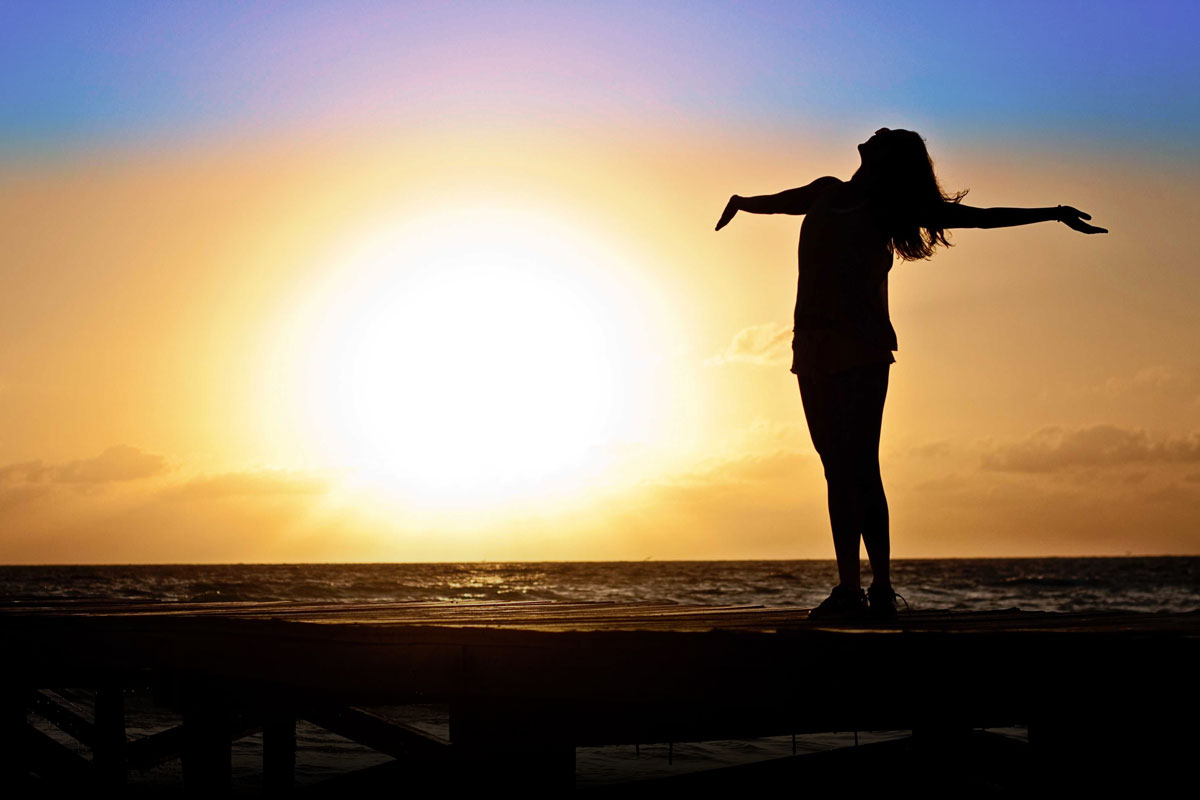 Woman with arms open on boardwalk at sunset